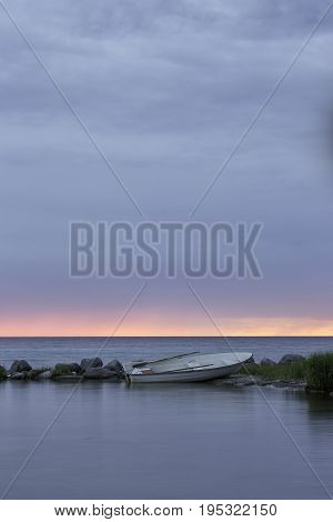 Rowboat by Ocean at Sunset with a partly cloudy sky.