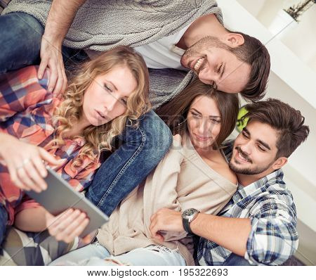 Group of friends taking selfie photo with tablet at modern home indoors.