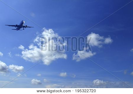 commercial airplane flying over sunny cloudy sky