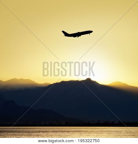 commercial airplane flying over mountains with clear sunset sky