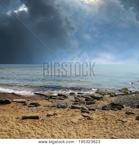 seascape image of sandy and rocky beach over stormy sky