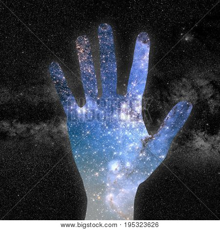 conceptual image of hand and abstract lights of universe.