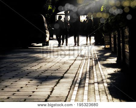silhouetted  people walking on street and sunbeam
