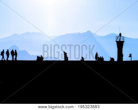 silhouetted people walking over sunny blue sky