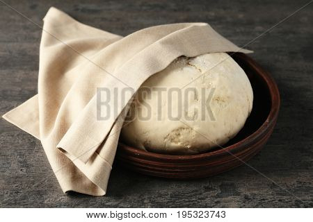 Bowl with raw dough on grey table