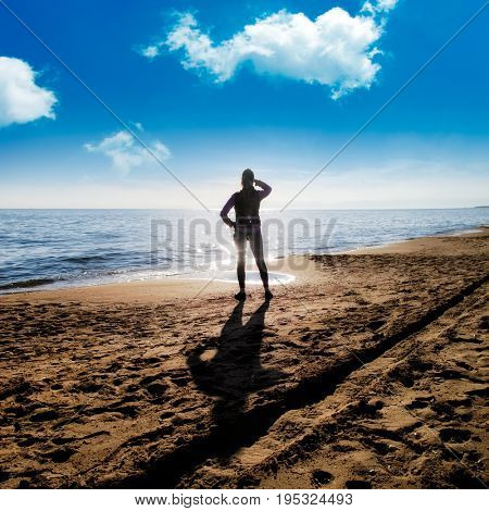 young adult woman walking on sandy beach