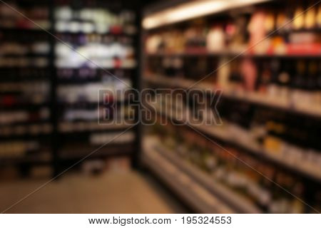 Blurred view of different kinds of wine on shelves in shop