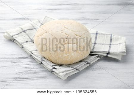 Ball of raw dough and napkin on wooden table