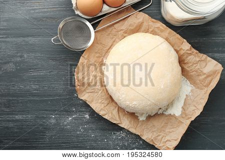 Food paper with ball of raw dough on wooden table