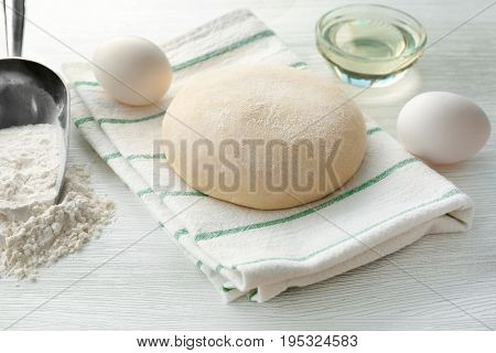 Ball of raw dough and ingredients on light background
