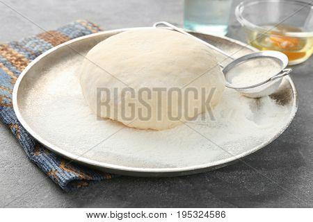 Tray with raw dough on grey table