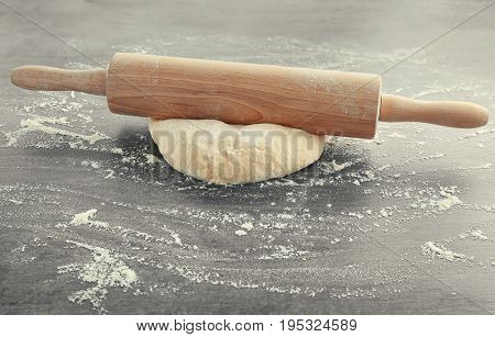 Raw dough and rolling pin on grey table