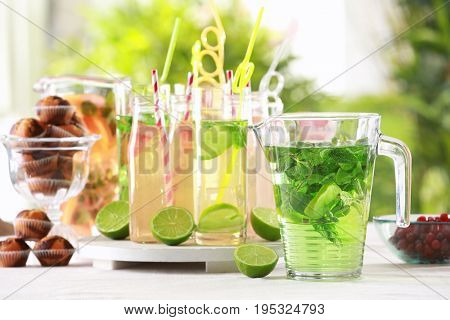 Glassware with different kinds of lemonade on table outdoor