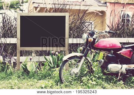 Wooden frame blank with copy space and old classic motorbike in countryside.