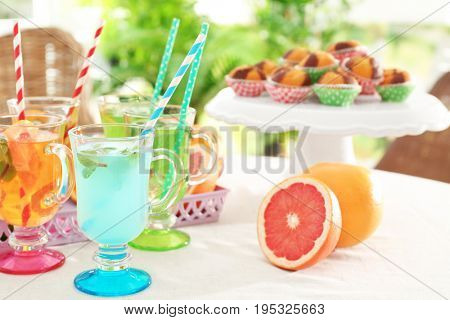 Glasses with different kinds of lemonade on table, outdoor