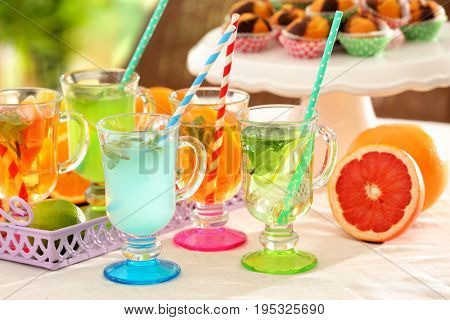 Glasses with different kinds of lemonade on table outdoor