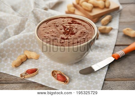 Bowl with creamy peanut butter on table