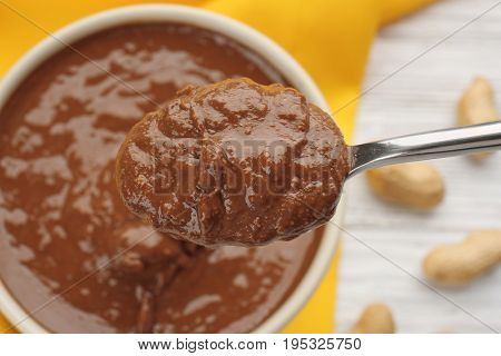 Spoon with creamy peanut butter, closeup