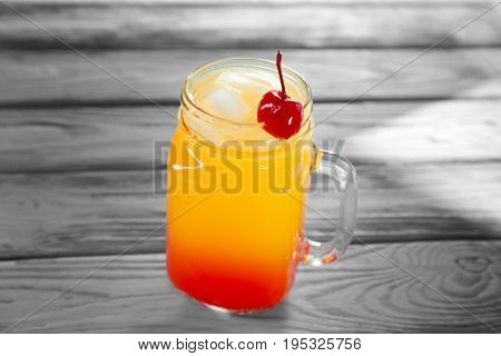 Mason jar of delicious tequila sunrise cocktail on table