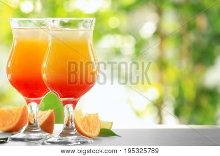 Glasses of delicious tequila sunrise cocktails on table