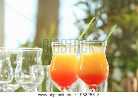 Glasses of delicious tequila sunrise cocktails on blurred background