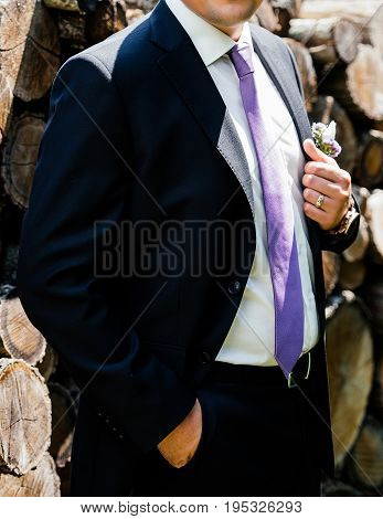 Stylish Groom In Black Suit, Tie And Boutonniere Outdoors Close Up. Groom Standing And Holding The C