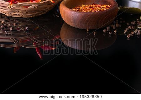 Spices and herbs, red chili peppers, black peppercorn and wooden bowl of chili flakes on black background with reflection