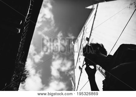 man smokes a cigarette in the shadows against the sky and buildings