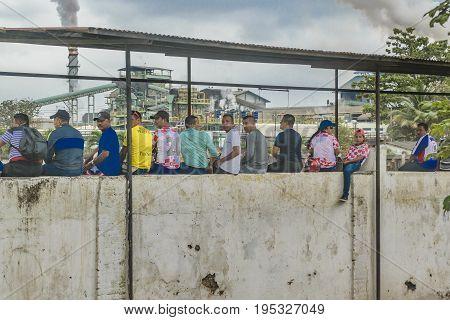 GUAYAS, ECUADOR, OCTOBER - 2016 - Group of adult men over wall watching a soccer game at Guayas district Ecuador