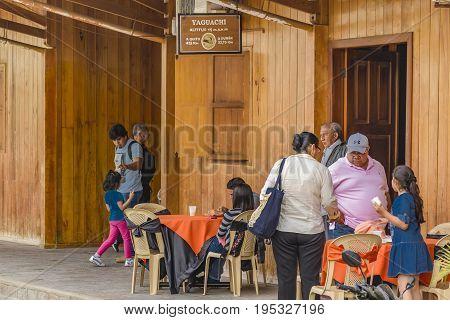 YAGUACHI, ECUADOR, OCTOBER - 2016 - Group of people at outdoor restaurant at small train station in Yaguachi town Ecuador