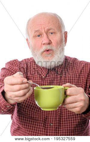 Cheerful and smiling handsome bald and bearded senior man with big green cup and teaspoon, isolated on white background