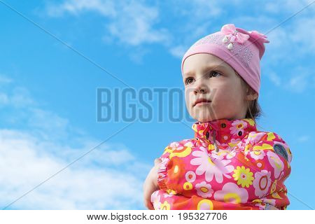 Little girl standing with folded hands gazing into the distance. Emotions commitment thoughtfulness seriousness anger resentment loneliness reverie She frowned angry dark and lonely