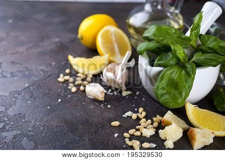 Ingredients for making pesto sauce on a black stone background, top view