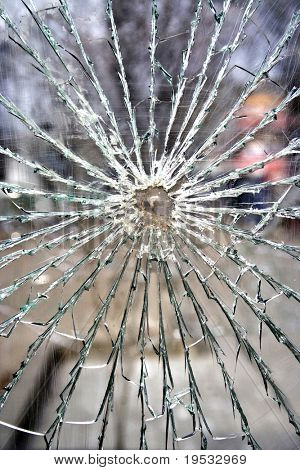 Broken glass-cracked windshield with hole over black