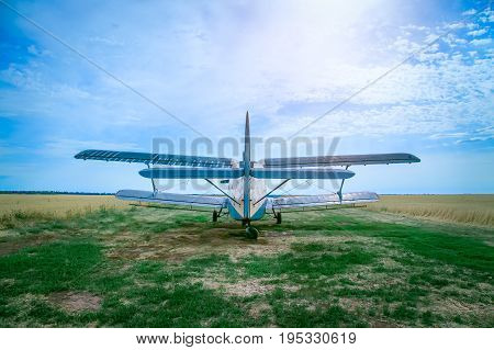 Agricultural plane is standing on a fieldRear view photo of an airplane. It stands on a wheat field. Blue cloudy sky is in the background.