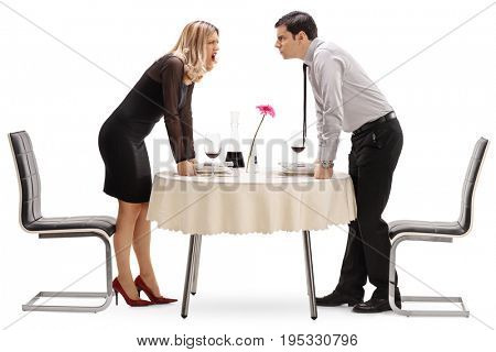 Young couple having an argument at a restaurant table isolated on white background