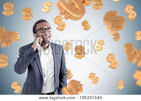 Portrait of a young and handsome African American businessman wearing glasses and a suit talking on a phone and smiling. Gray background dollar signs