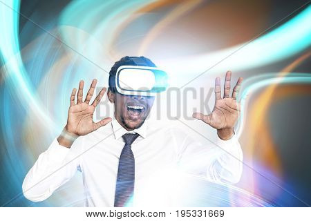 Portrait of a young excited African American businessman wearing VR glasses and smiling. He is standing against an abstract background. Double exposure toned image