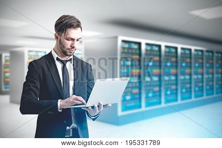 Close up of a bearded engineer standing with a laptop in a server room with polygons hologram behind him. 3d rendering mock up toned image double exposure film effect