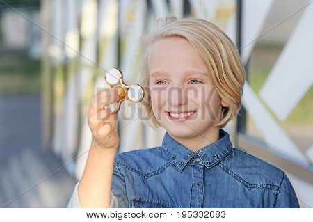 Beautiful cheerful school girl playing with a gold fidget spinner. A popular trendy toy for the development of fine motor skills in children and adults.