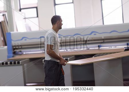 Young worker works in a factory for the production of wooden furniture