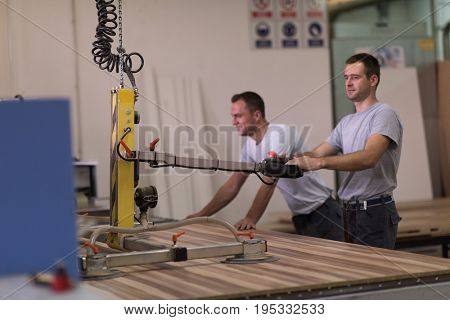 two worker working in a factory for the production of wooden furniture