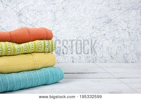 Knitted wool sweaters. Pile of knitted summer clothes on wooden background, sweaters, knitwear, space for text