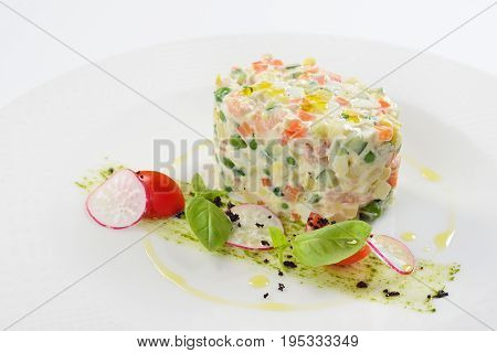 Traditional Russian food salad olivie with shrimps. White background menu concept.
