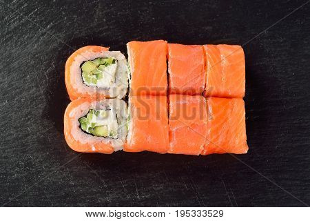 Sushi rolls Philadelphia with salmon cucumber and soft cheese on a black slate surface menu concept.