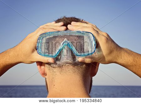 A man in a diving mask stands behind. Summer leisure concept