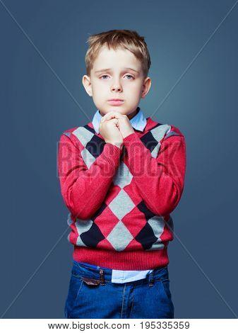 unhappy little boy, isolated against grey