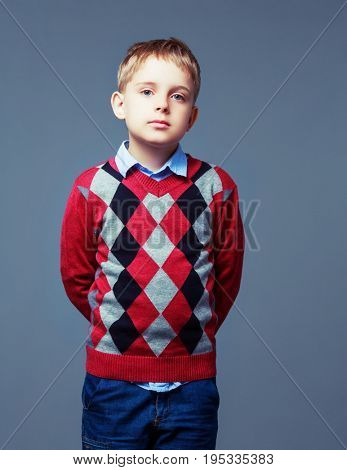 nautral emotion on the face of a boy isolated against grey background