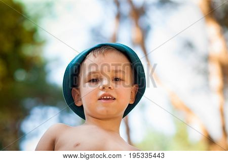 Outdoor close up portrait of little boy in a hat. Background, one person, child, 4-5 years old, happy smilling, summer day.
