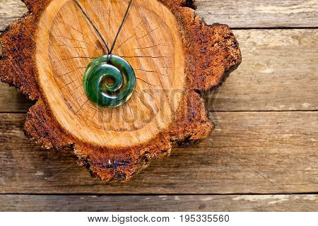 Maori New Zealand Greenstone pounamu jade Koru (spiral fern) shape pendant on cross section of timber log on wooden plank background
